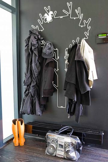 A wire tree coatrack adds a playful, graphic touch to a charcoal entryway.