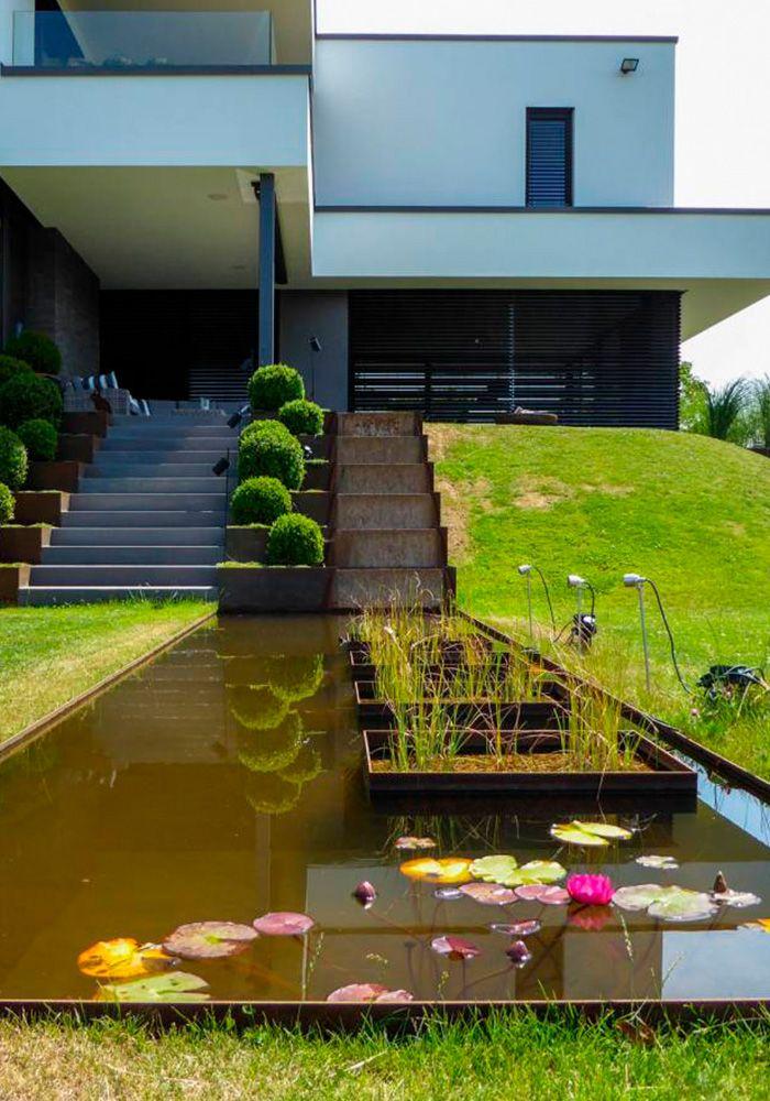 Minimalistische Gartengestaltung am Hang mit Wasserbecken aus - eine feuerstelle am pool