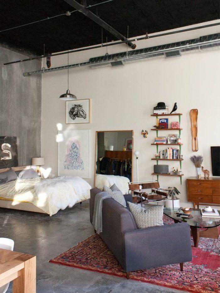 Studio sol et murs en béton gris, tapis oriental rouge, canapé ...
