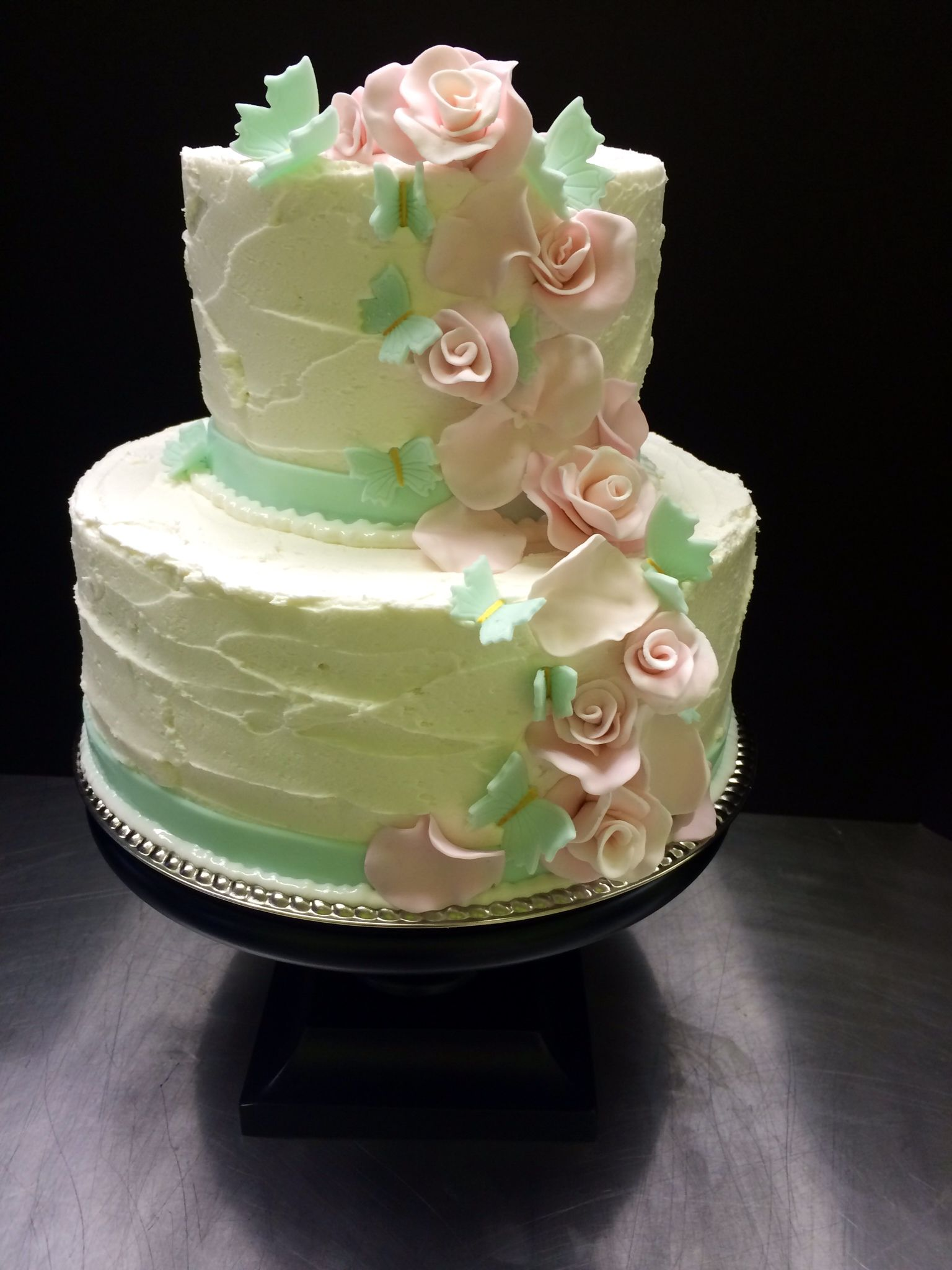 Simple buttercream wedding cake with Pink flowers and aqua