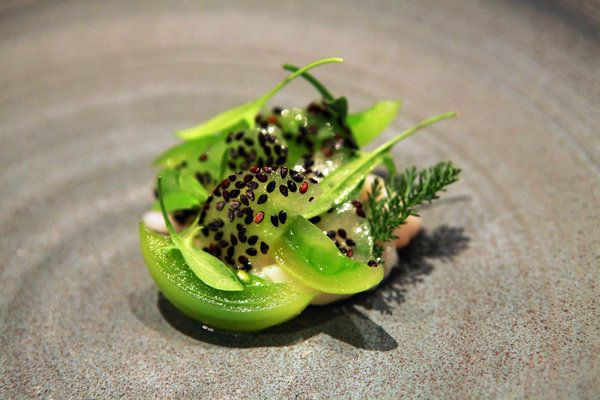 "Oh, the colors! The dish sounds mighty fine, as well. ""Raw scallops cured in gin botanicals are interwoven with shards of green tomato ice, a scattering of black sesame seeds on top."" Credit: Hiroko Masuike/The New York Times"
