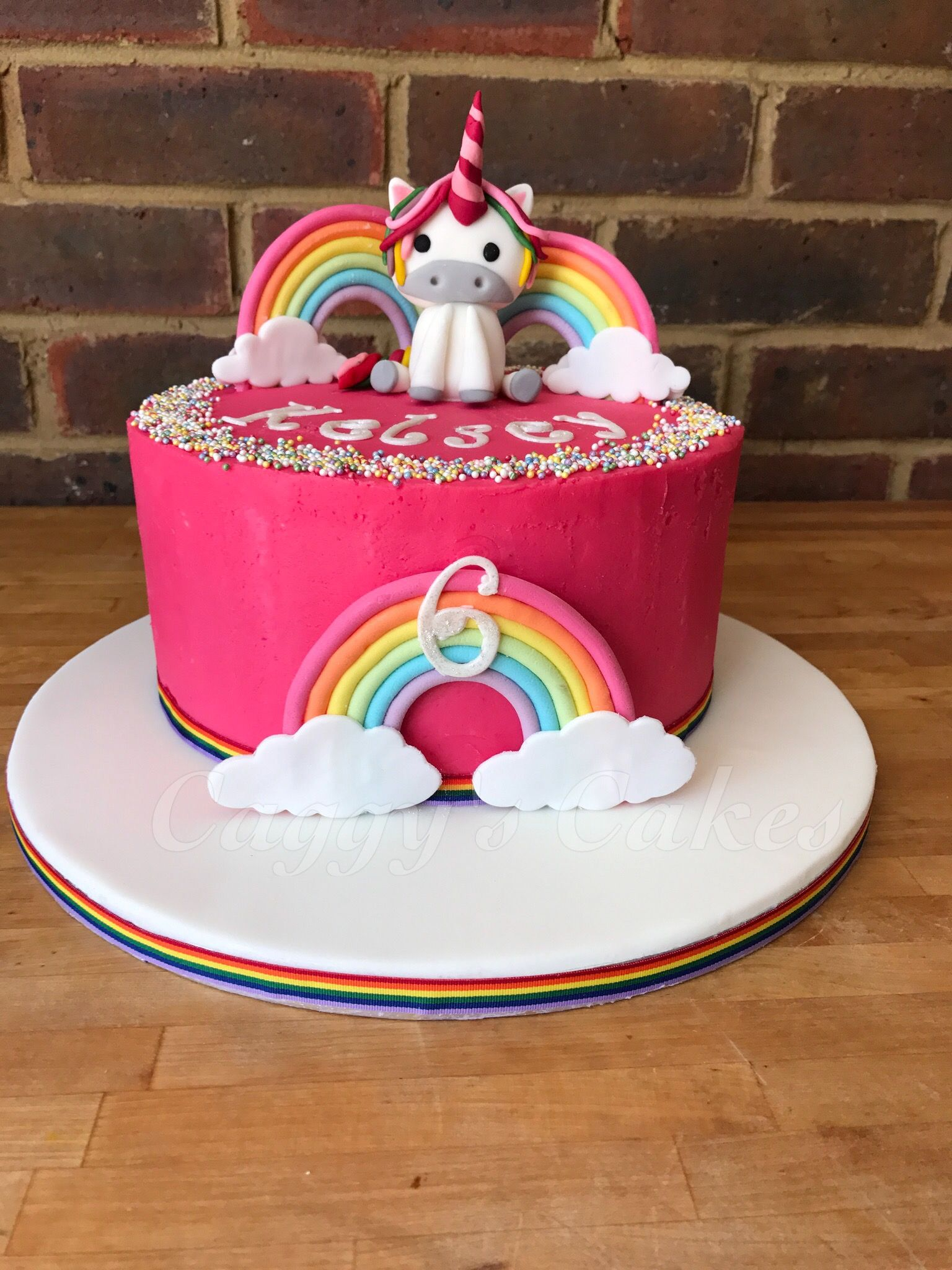 Strawberry buttercream cake with handmade unicorn and rainbows with