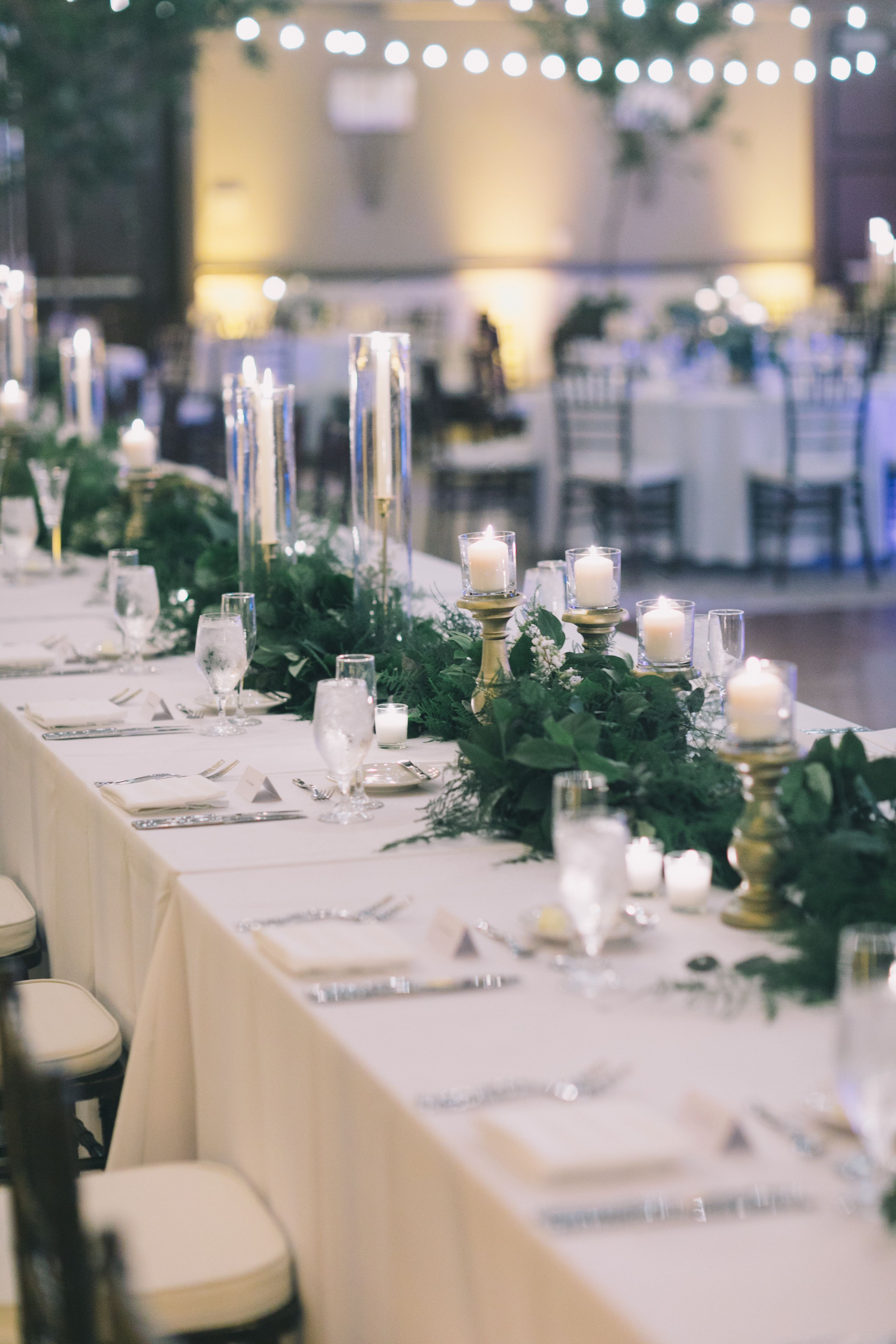 Head Table Dressed With White Linens Gold Pillar Candles
