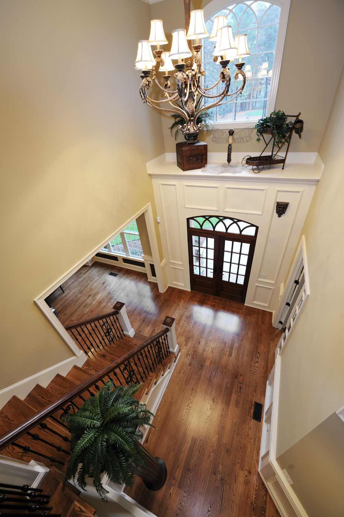 A view of the above foyer from the top of the staircase landing, showing the shelf above the doors, the large light fixture, and the fern topping the dark column.