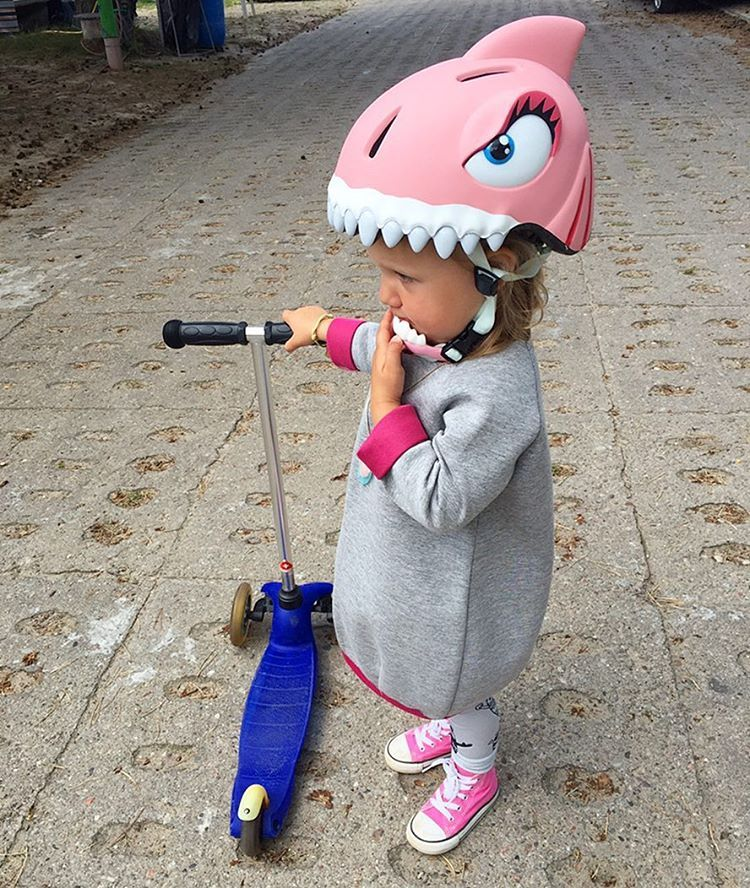 Hero of the day Little shy girl in a pink shark helmet