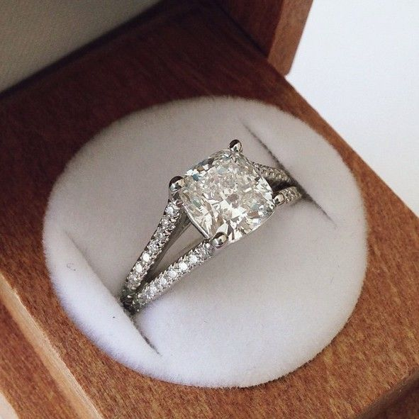 A shimmering halo of pavé-set diamonds encircles the center diamond this glimmering ring. A diamond accented split shank band adds a glamorous effect.