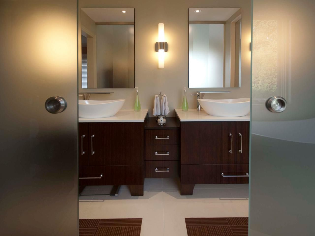 This elegant, contemporary bathroom has his-and-hers vanities and matching medicine cabinets. The frosted, sliding glass doors allow daylight to filter through the entire space.
