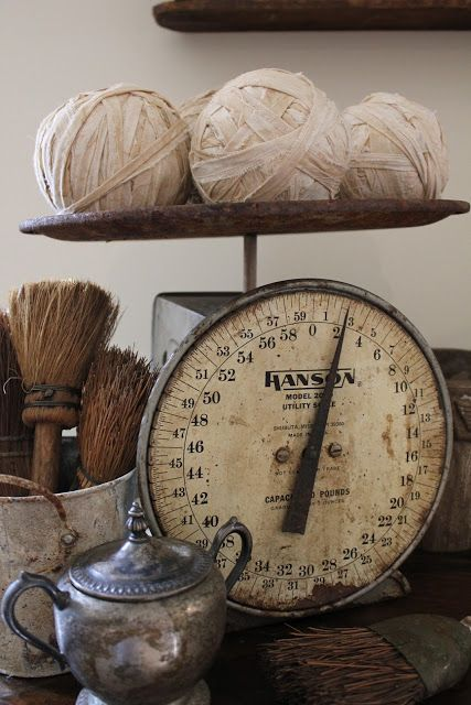 Neutrals An Antique Scale With Ragballs Placed On Top A