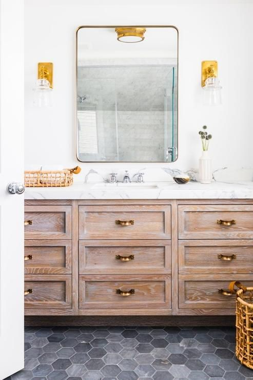 Restoration Hardware Bristol Flat Mirror, illuminated by glass and brass bell jar sconces, stands over a limed brushed oak washstand adorned with antique brass pulls topped with white marble fitted with a polished nickel faucet alongside a black hex tile floor.
