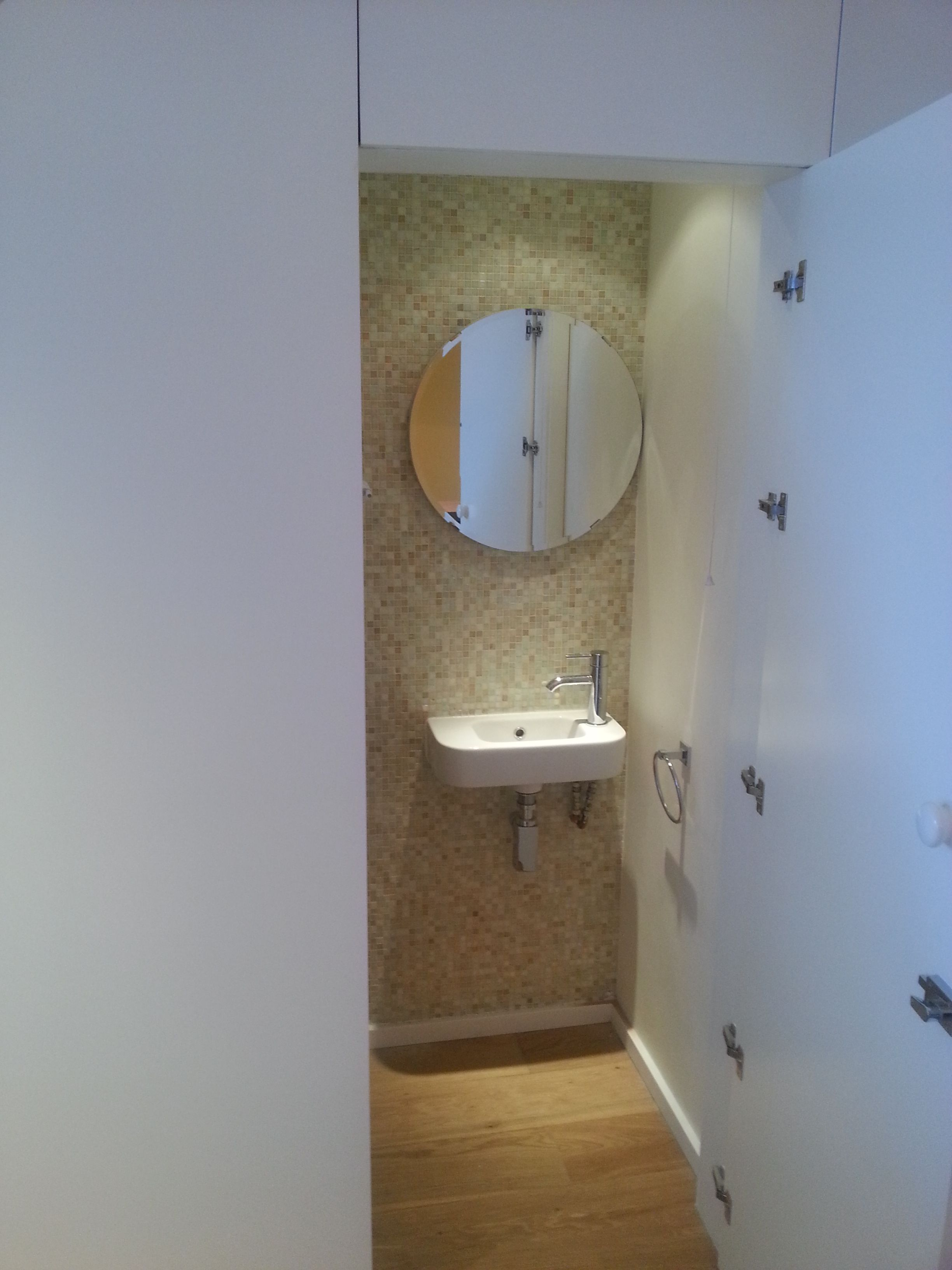 Toilet under stair covered by at white matt finisihing panneling