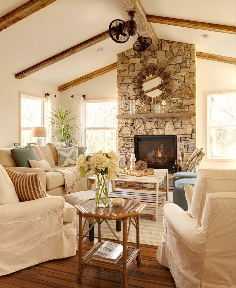 vaulted ceiling with wood beams, natural stone fireplace, and
