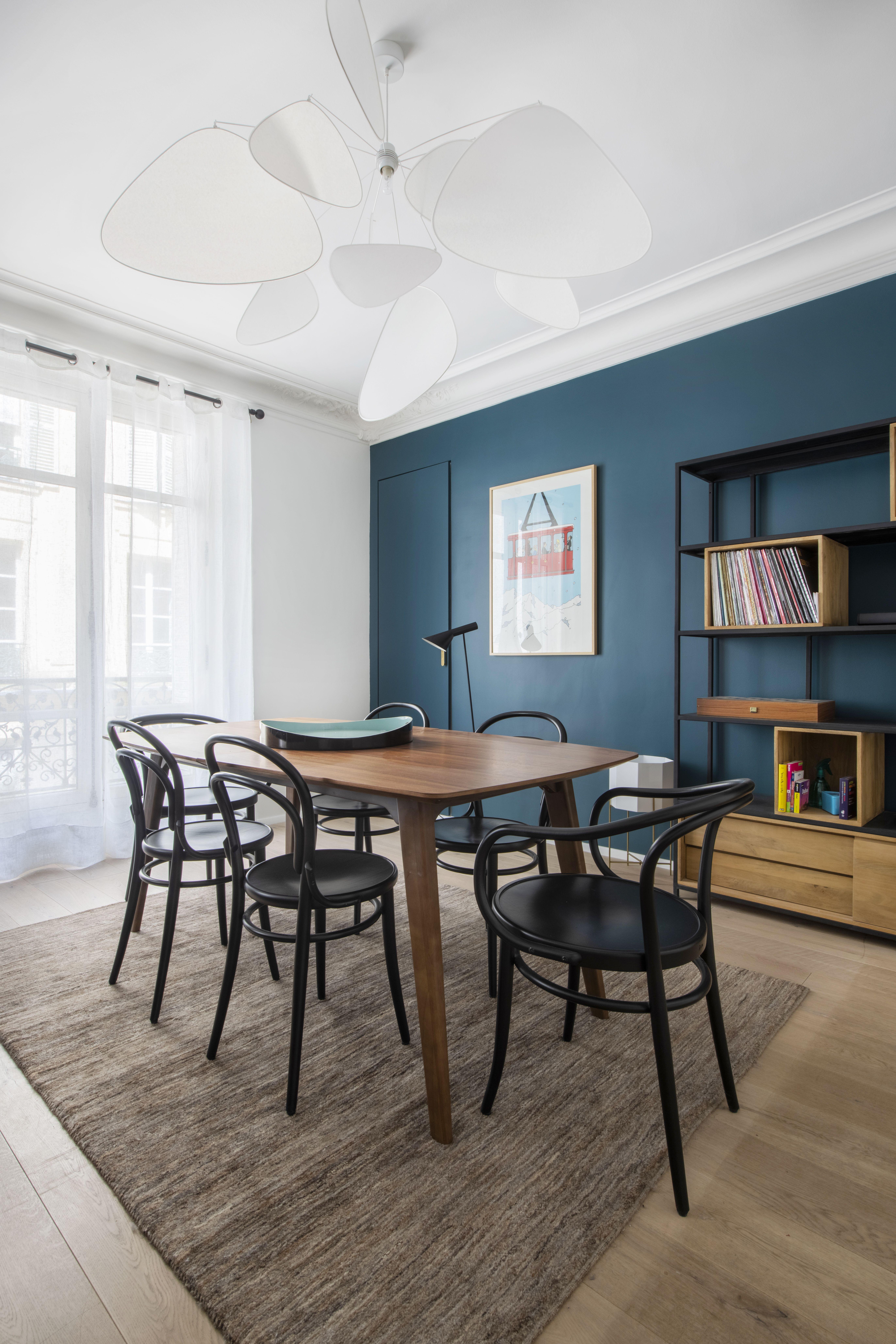 Salle à manger avec table en bois et chaises noies, mur peint en bleu avec bibliothèque et suspension design blanche #Renovation #architecture #ideas #hacks #Maison #Design #House #Budget #Budgethomedecor #salleàmanger #dinningroom