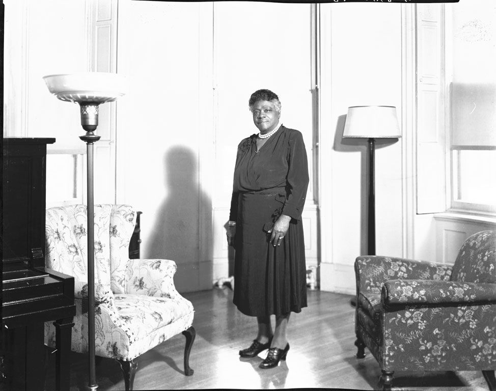 [Mary McLeod Bethune standing in room, near chairs