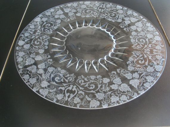 Up for sale is this Etched Glass 14 1/8 Inch Platter With Leaves & Grape Design with no chips or cracks. Some scratching from use. The Etching is on the reverse. Everything we offer at auctions is pre - owned &/or used. This item(s) may show some signs of wear commensurate with age & normal use.  Shipping Excludes: Alaska/Hawaii, US Protectorates, APO/FPO, PO Box Shipping Provided to the United States Only