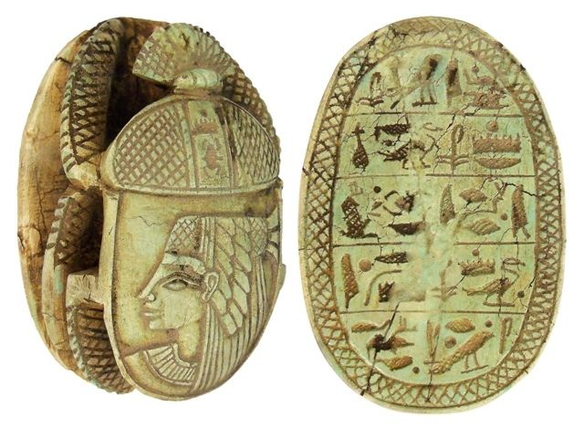 """Carved light green limestone heart scarab, once placed on the throat, chest, or heart of the mummy. Some were worn by the deceased on a necklace, or mounted in gold settings as a pectoral. Heart scarabs provided the bearer with the assurance that at the final judgment as depicted in the Book of the Dead, the bearer would be found """"True of Voice"""" and accepted into the eternal afterlife by the God Osiris. With open fretwork, a beetle and a portrait of a Goddess on the top, five lines of…"""