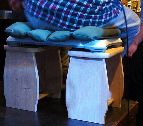 Wiiバランスボードを使って開発した体重計測用の椅子。といっても、木製の台を2つ並べたものに、クッションを載せただけ
