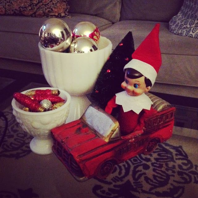 Elf on the Shelf, Lollie Gags, is taking a ride in the vintage fire truck planter - Primitive and Proper