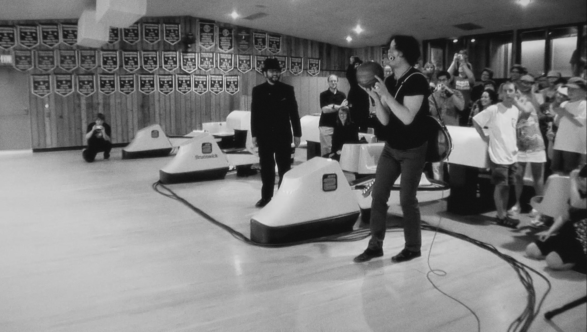 white stripes playing a surprise show in a bowling alley