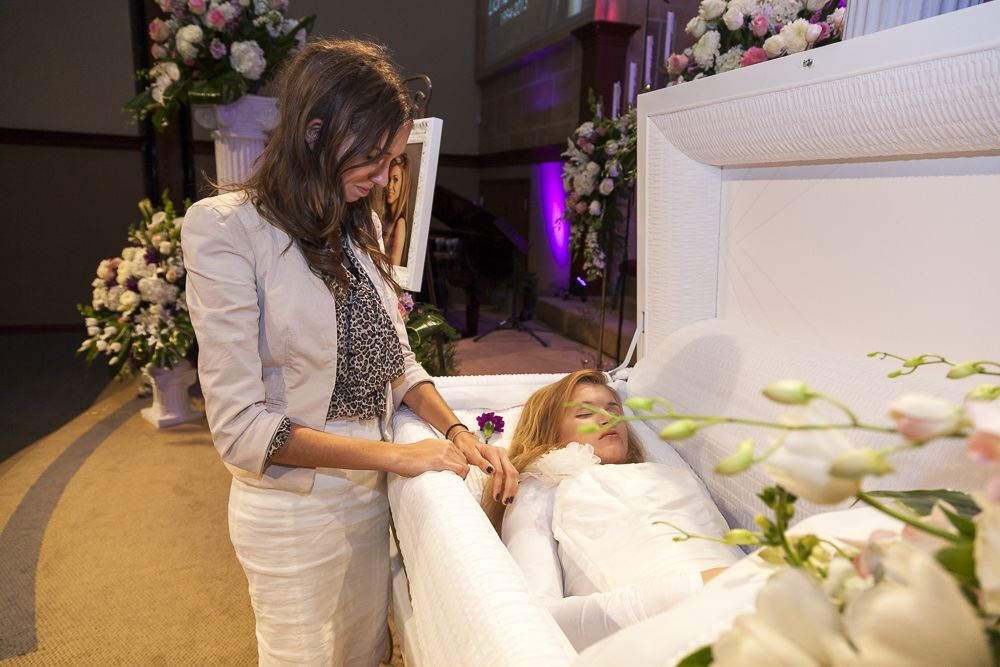 Liana Kotsura's sister caresses her during her open casket funeral.