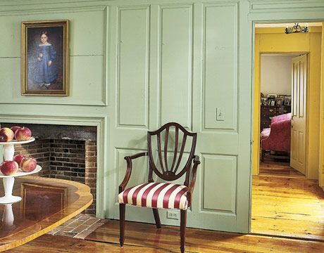 A Dining Room in Painted and Paneled Walls with a Federal Style Chair, a Mahogany Dining Tabe, and a Folkart Portrait of a young girl in a Blue Dress.
