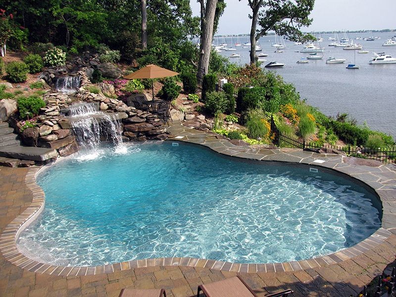 Luxury Swimming Pools With Waterfalls freeform pool with rock waterfall, lush landscaping, sunshine, and