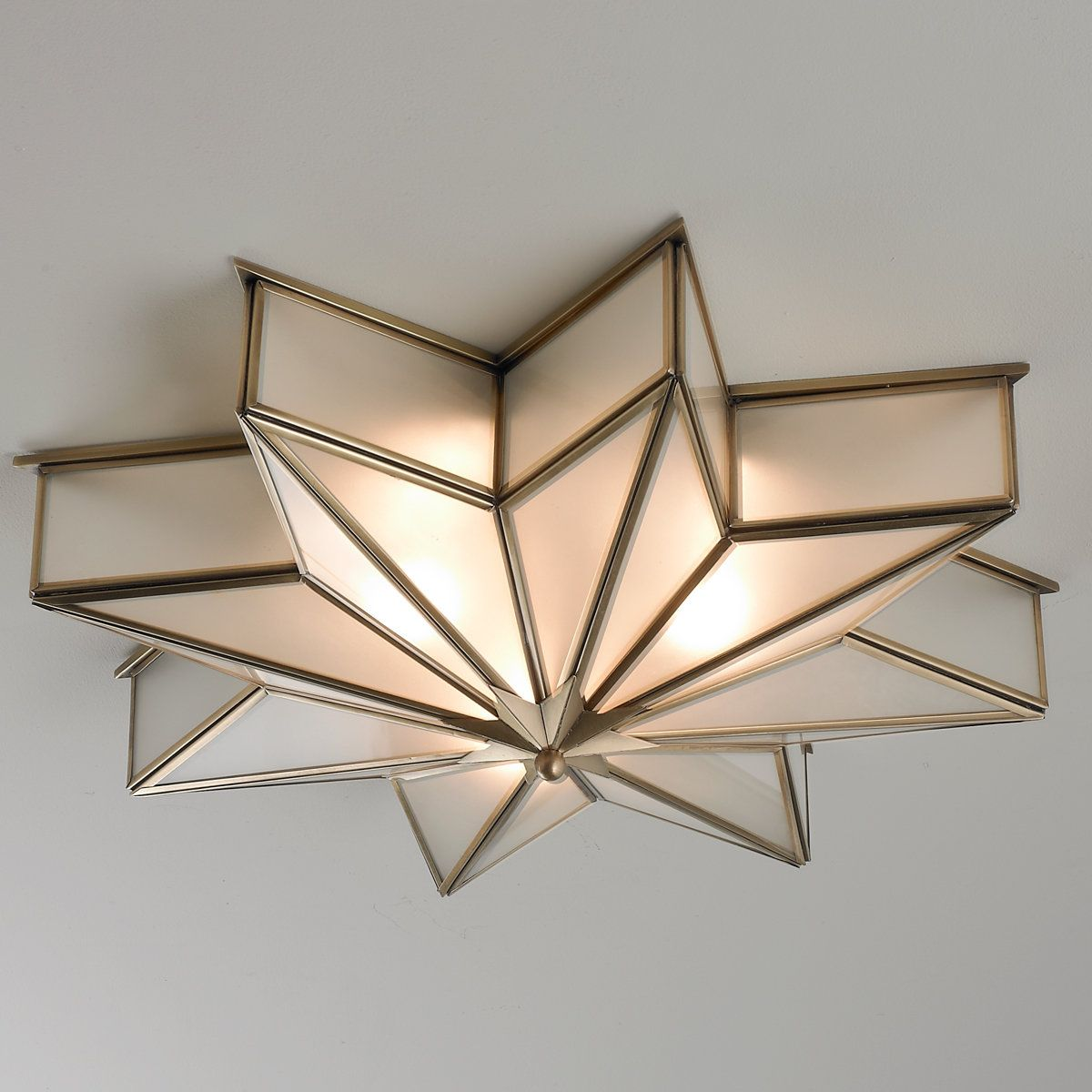 The magic of Hollywood stars comes alive in this 8 point star flush mount light in glare free frosted glass trimmed with satin brass.