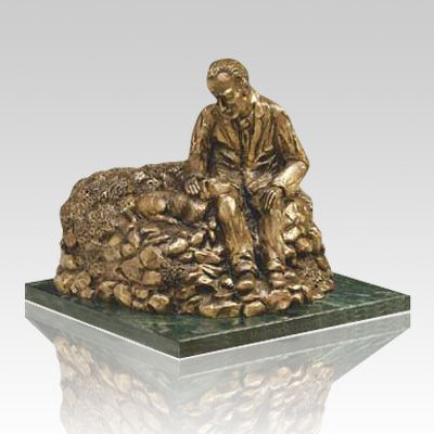 The Man Resting Cremation Urn features a man resting with his loyal companion and is made by the lost wax cast bronze method with a natural bronze patina. A protective lacquer finish is put on as a final touch. Mounted on a deep green marble base.  Bottom opening base attaches with screws.