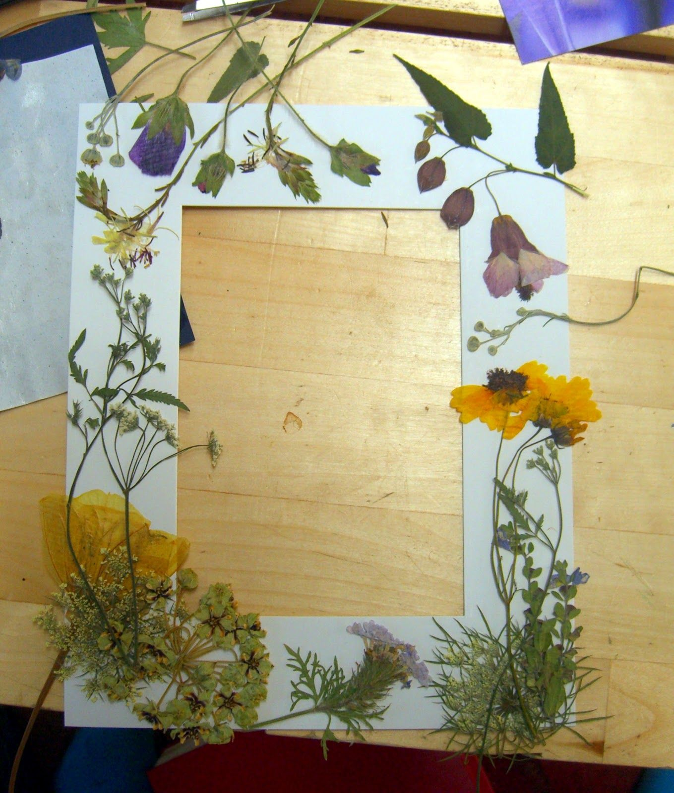 Decoupage pressed flowers to a photo mat board.
