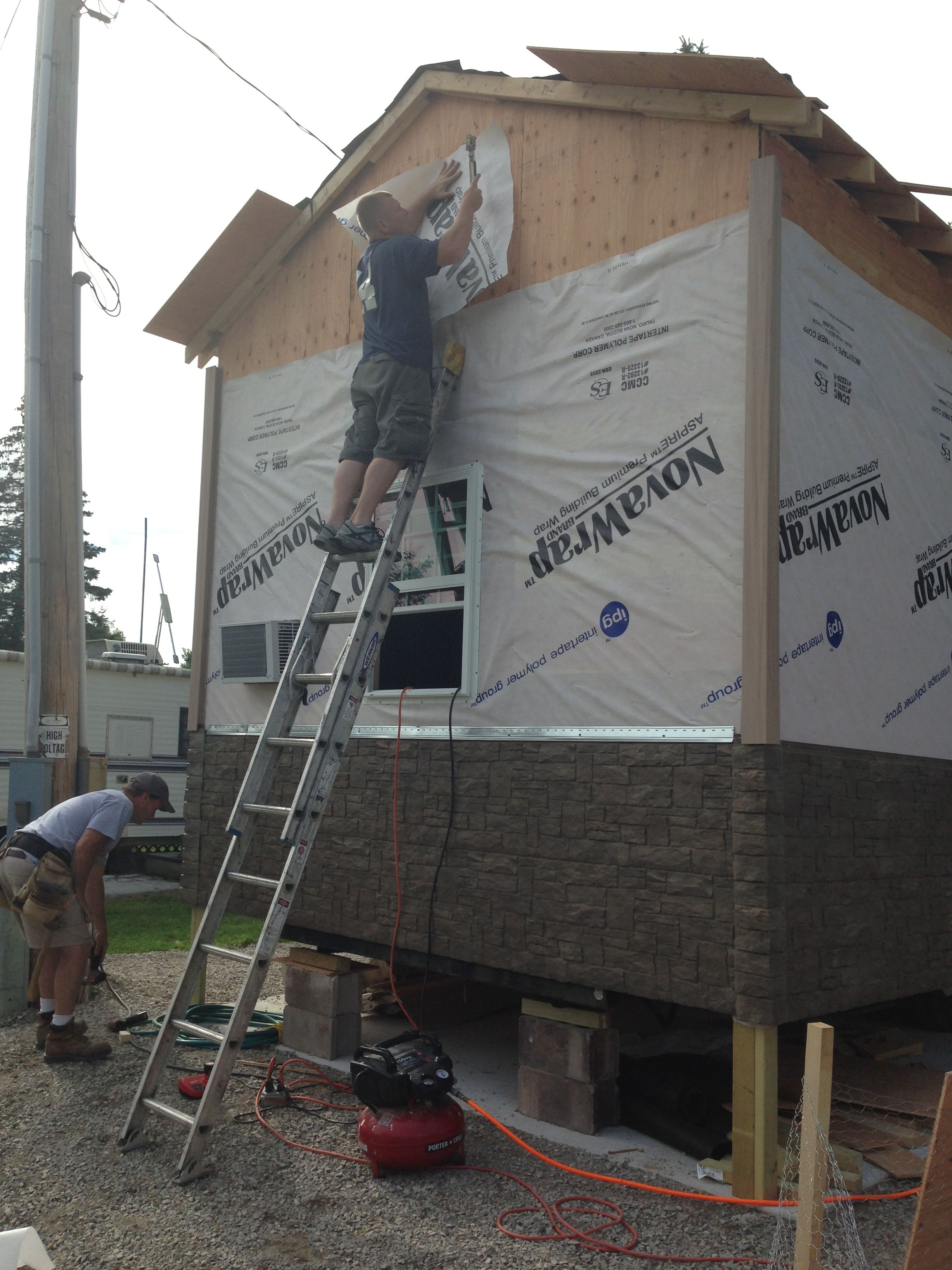 Finishing The House Wrap Insulation That Precedes The Siding With Images House Wrap Insulation Park Homes House