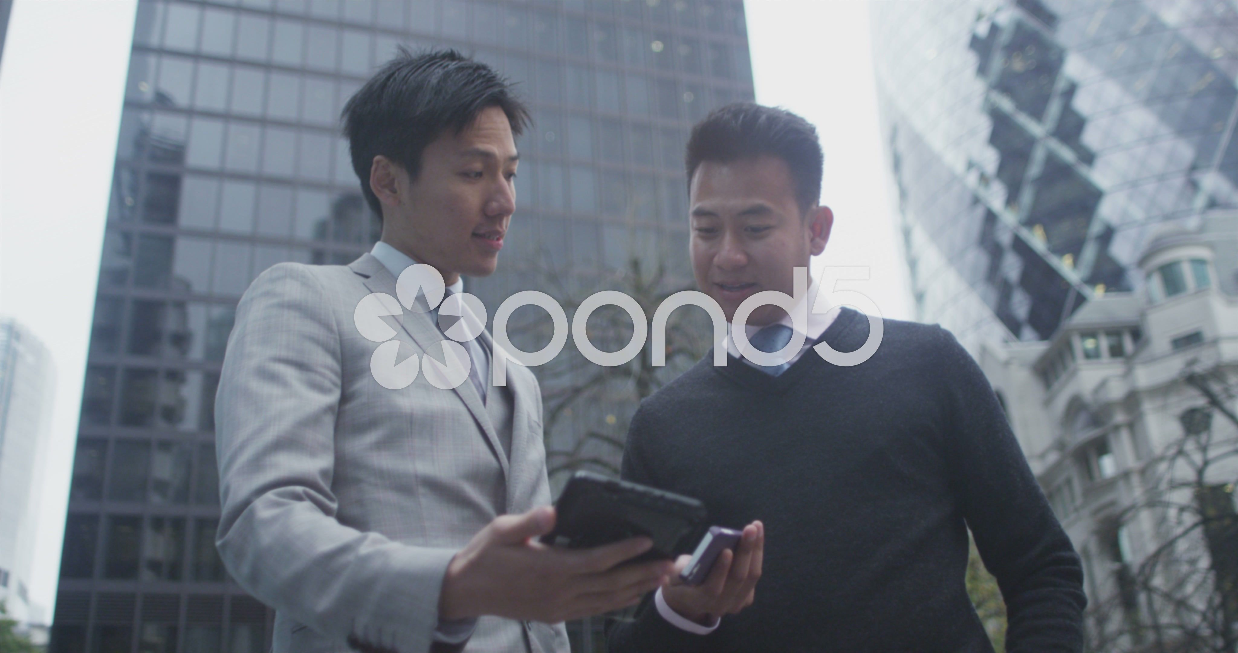 4k Portrait Of 2 Cheerful Asian Businessmen Chatting Outdoors In
