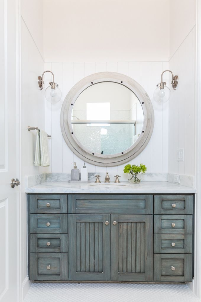 Beach House Bathroom This Features Vertical Shiplap Walls Lined With A Large Gray Wood Mirror Illuminated By Clear Glass Barn Sconce Over