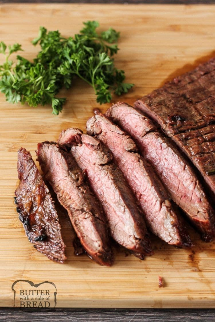 sliced flank steak on a wooden cutting board #recipesforflanksteak