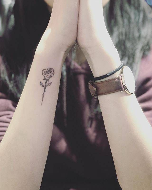 Fine line rose tattoo on the wrist.