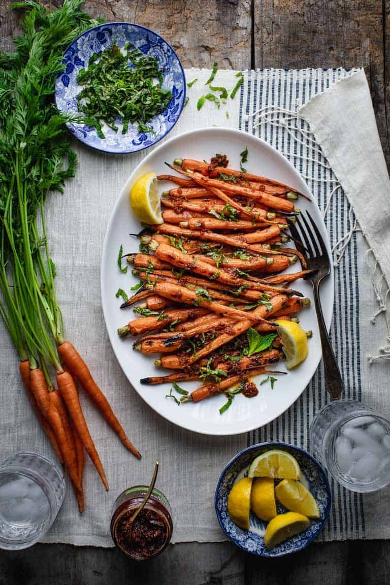 The key to Tender Grilled Carrots (without burning) is to grill them over indirect heat. This foolproof recipe for grilled carrots is topped with harissa, lemon and mint. Absolutely delicious, vegan and gluten free! #grilled #carrots #harissa #vegan #healthy #glutenfree