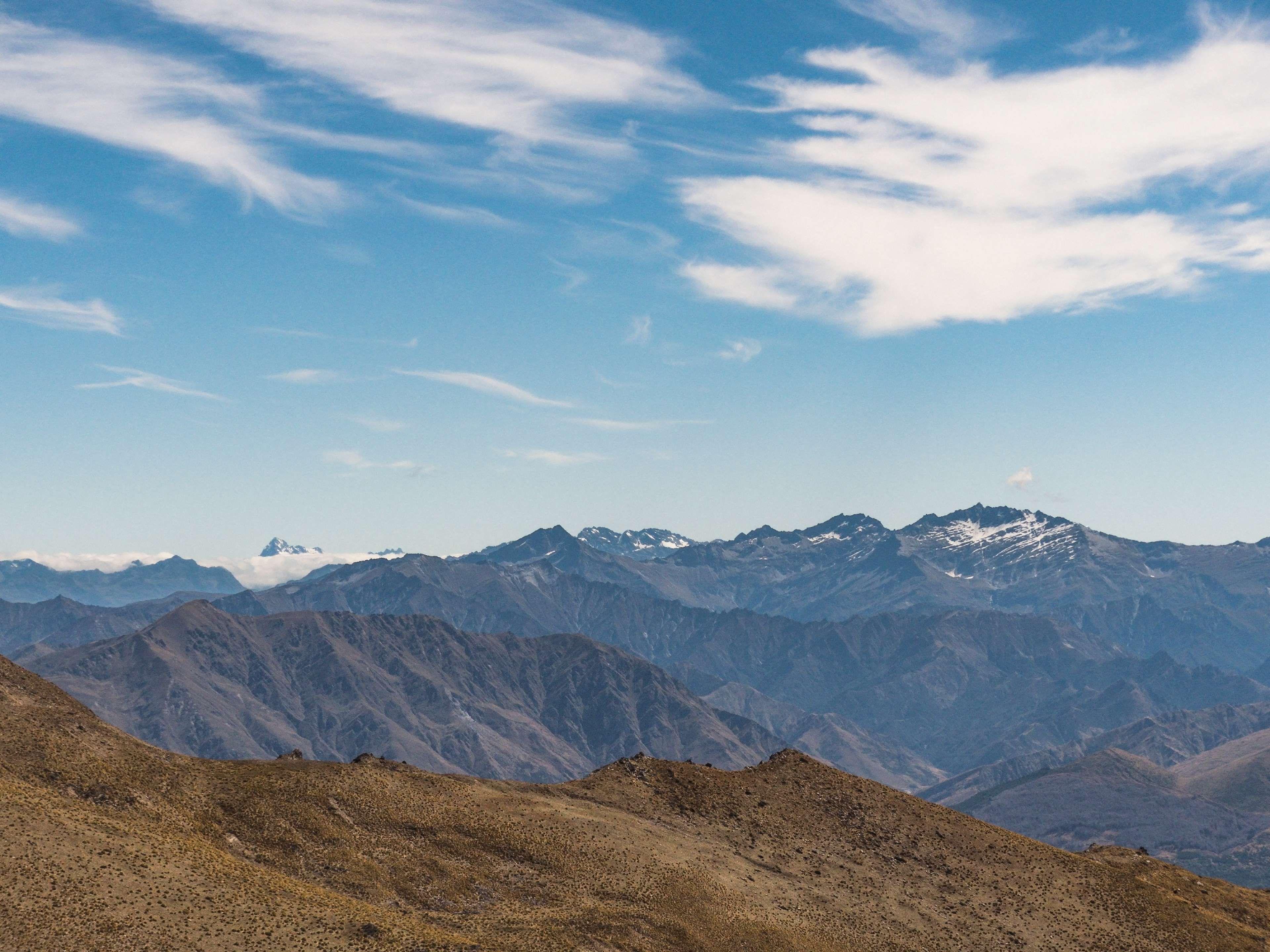 adventure blue sky clouds distance fade hills mountain range