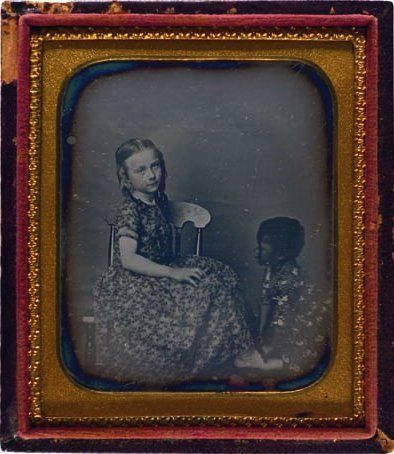 (c.1840s-1850s) A young girl with a Black American slave child at her feet