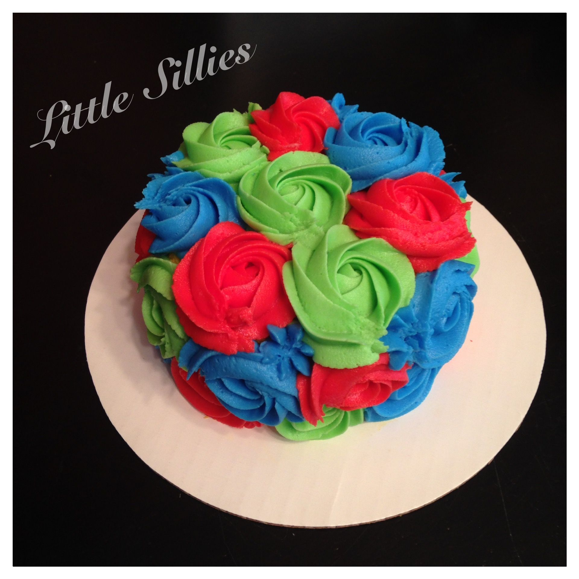 A multi-colored rosette smash cake