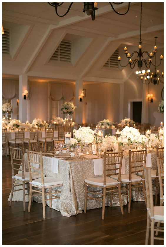 Gold, ivory and white wedding reception decor with white florals in glass vessels, place