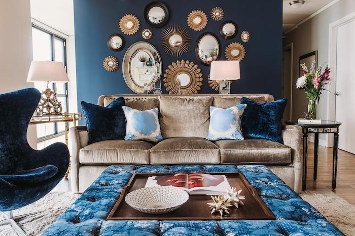 fauteuil velours, murs blancs avec une partie peint en bleu, mur de miroirs soleil, table noire en verre, bouquet de fleur, vase en verre #wanddekowohnzimmer