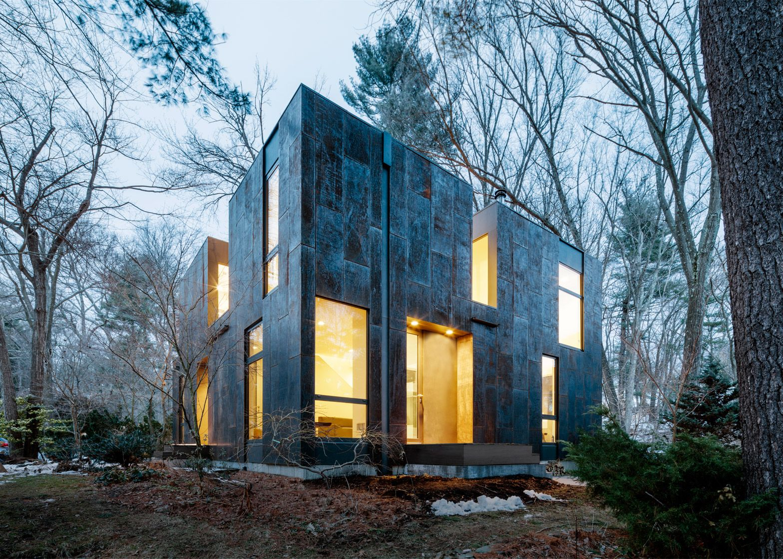 Merge clads compact massachusetts home in weathering steel