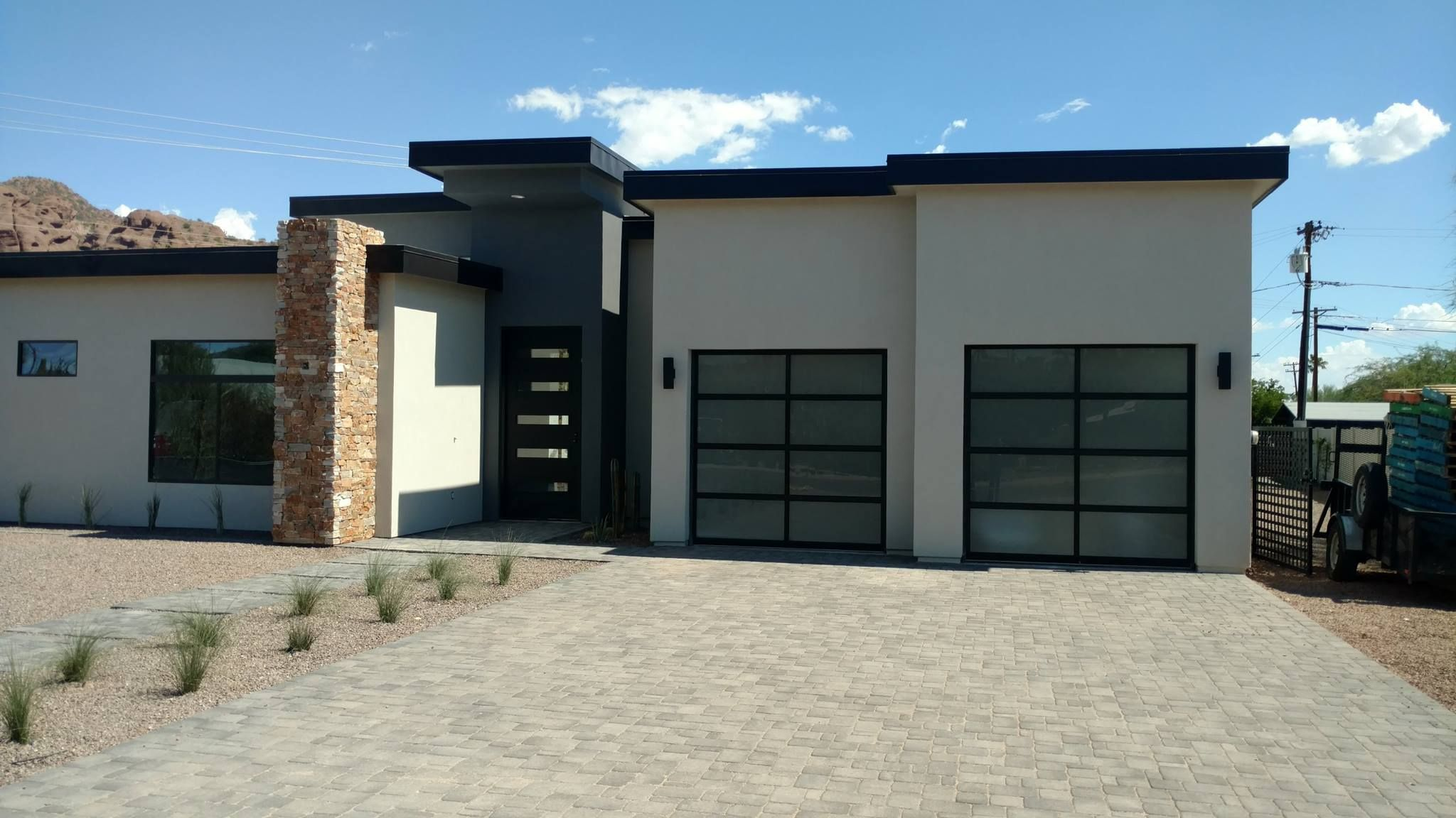Clopay Avante Collection Glass Garage Door On A Modern Home Black Aluminum Frame And Frosted Glass For Priv Garage Doors Modern Garage Doors Glass Garage Door