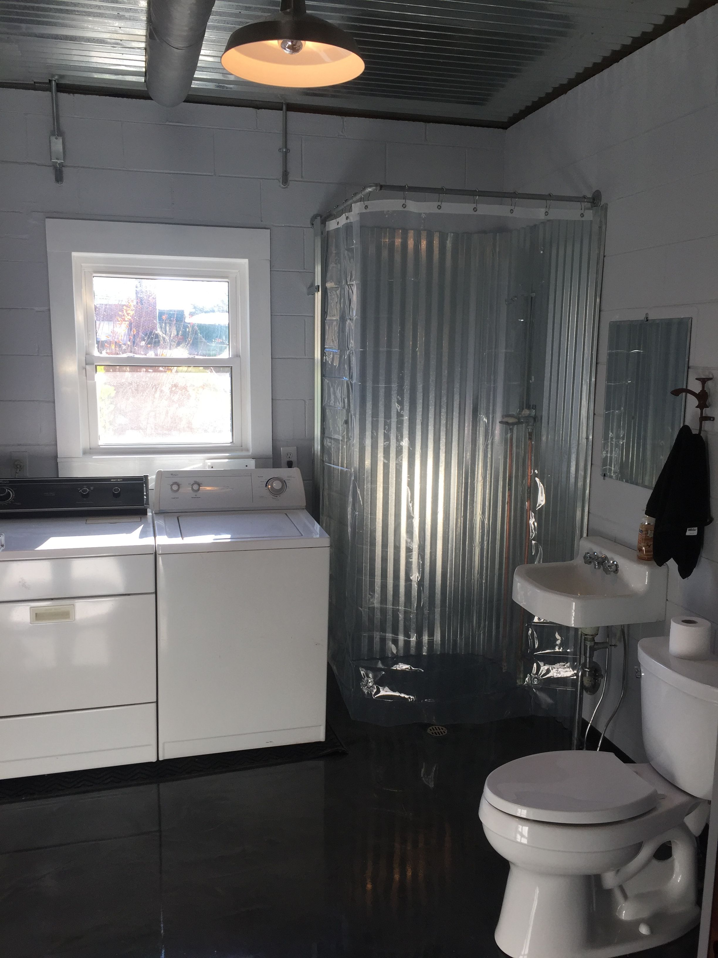 Basement bathroom with corrugated metal surround for shower walls