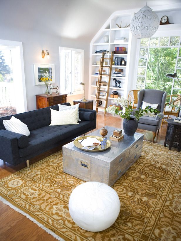All three styles are found in this eclectic living room modern sofa and steel trunk traditional wingback chair persian rug global moroccan pouf also