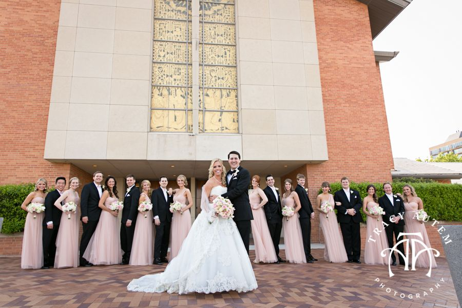 Whole entire bridal party stand behind the bride and groom in front of the Fort Worth 1st Presbyterian Church. Bride is wearing a beautiful lace ball gown from Stanley Korshack and holding a full boutique of pink and white roses. Bridesmaids are in long blush gowns. Groom and groomsmen are wearing standard black tux with black bow tie. Wedding Ceremony at Fort Worth 1st Presbyterian ChurchWedding Ceremony at Fort Worth 1st Presbyterian Church