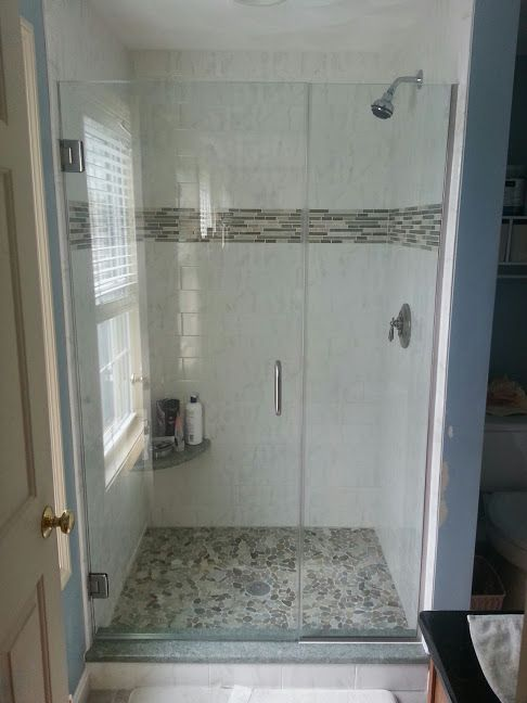 Frameless Shower Door With Chrome Hardware And Track Supporting The
