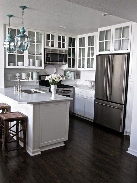White cabinets with dark floor  glass cabinet doors open up small kitchen Grace and Collin s Coastal Cottage Dark hardwood flooring