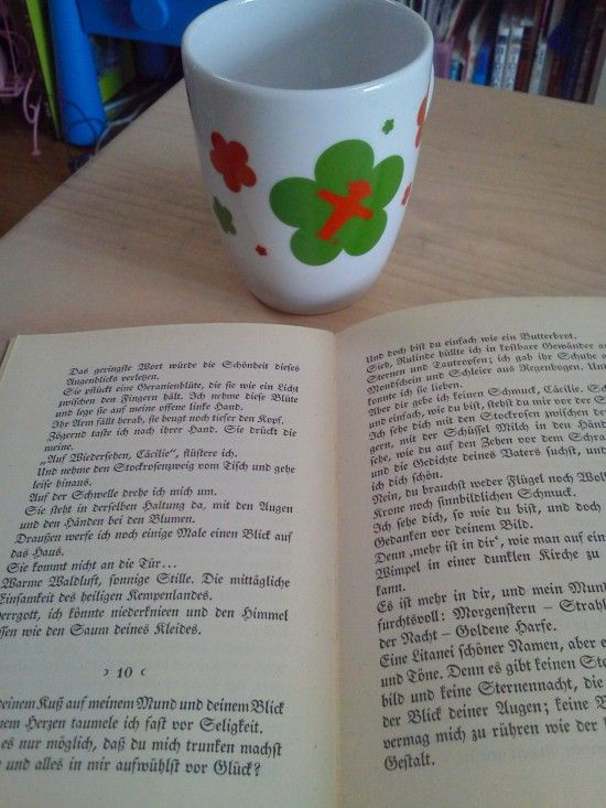 Old German Book opened and an Ampelmann (Signal man from old East German sector) Mug