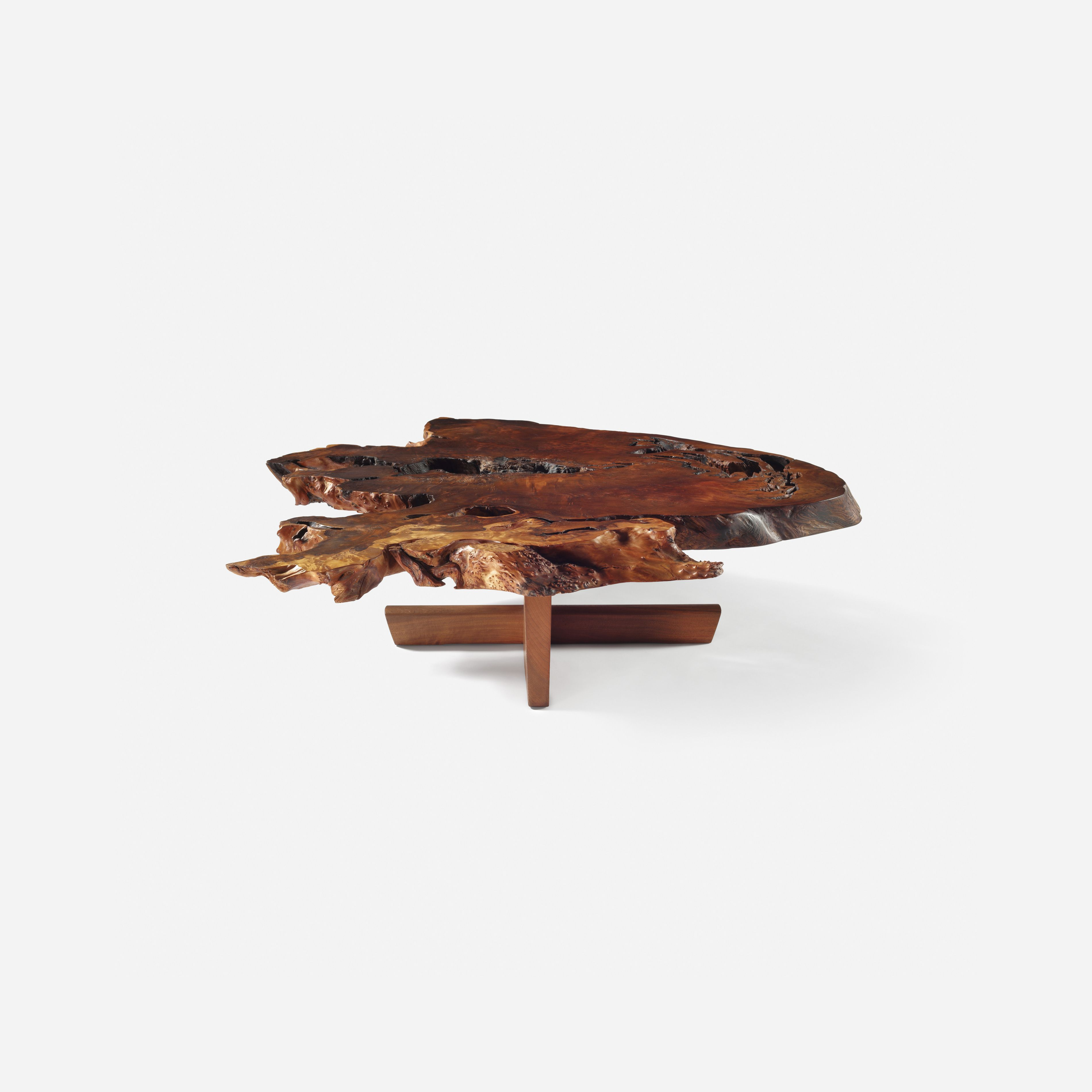 Lot 11: George Nakashima. Important and Rare Minguren coffee table. 1977, redwood root burl, American black walnut. 61¼ w x 53 d x 15¼ h in. estimate: $150,000–200,000. An exceptionally figured solid redwood slab top with sap grain detail, numerous fissures, burls, free edges and four walnut butterflies to underside. Client name to underside: [Hoffman]. Sold with a copy of the original order card and invoice and a letter of authentication from Mira Nakashima. Provenance: Acquired directly…