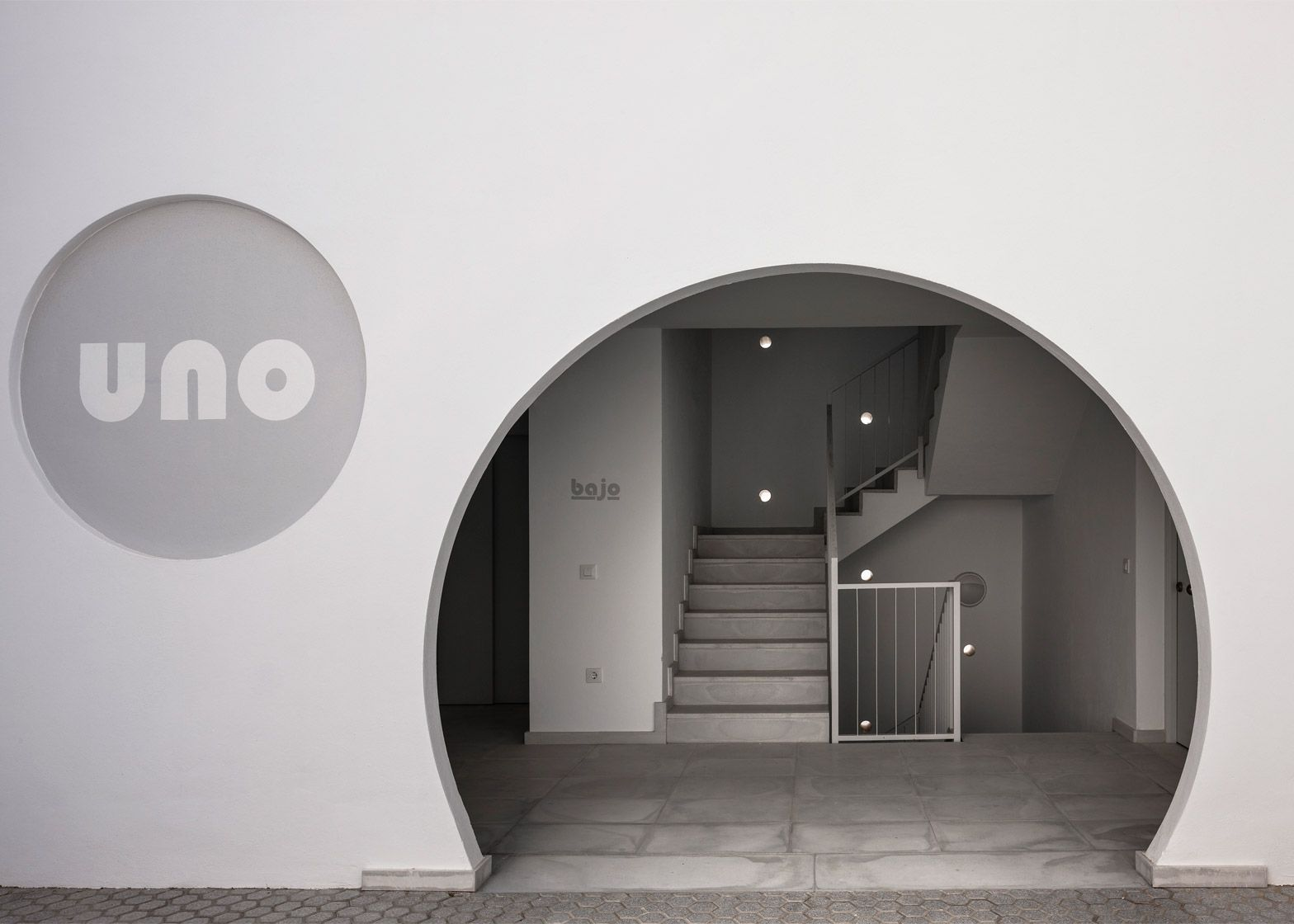 Circular openings form entrances and windows for this housing development in the Spanish town of Conil de la Frontera, designed by Seville studio Kauh