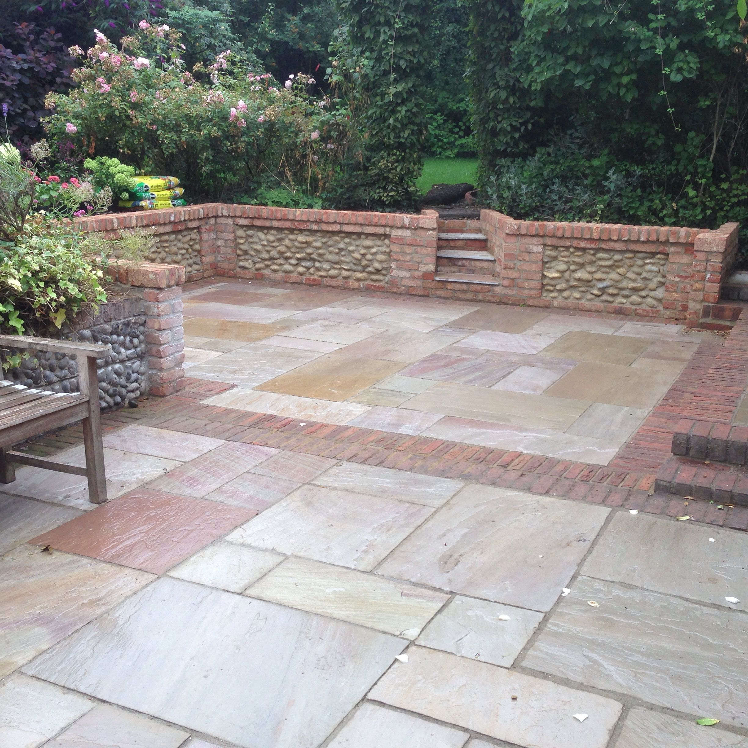 The sunken patio with brick and flint panel walls. The ...